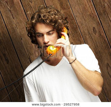 retrato de um jovem falando no telefone vintage contra uma parede de madeira