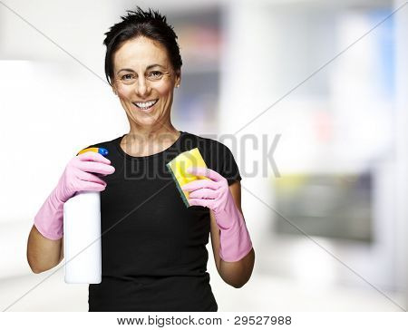 Middle aged woman holding a spray and scourer at kitchen