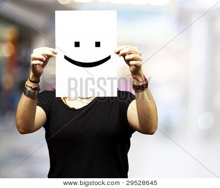 Woman showing a blank paper with a smile emoticon in front of her face at a crowded place