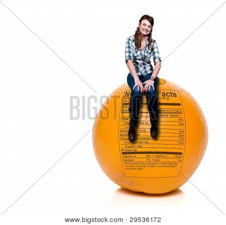 Woman Sitting On Orange With Nutrition Label