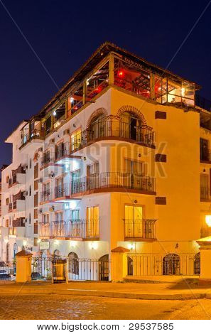 Nice hotel building with roof restaurant at night in Puerto Vallarta, Mexico.