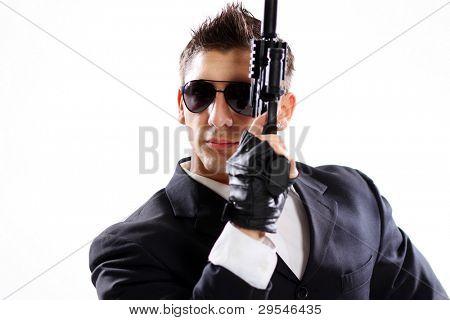 Joven en traje negro con pistola aislado sobre fondo blanco