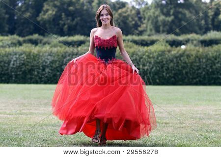 Smiling woman in a red dress walking on meadow in park