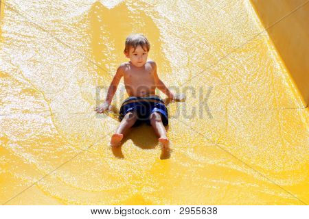 Young Boy Going Down A Waterslide