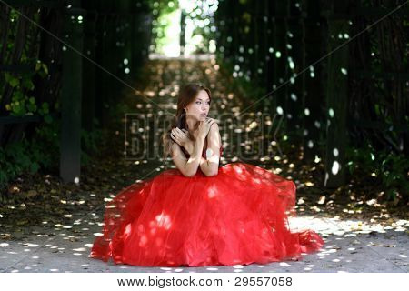 Beautiful woman in a red dress walking in alleyway in park