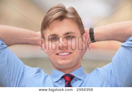 Young Businessman Holds Hands Behind Head