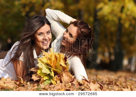 Smiling young attractive women with autumn maple leaves in park at fall outdoors