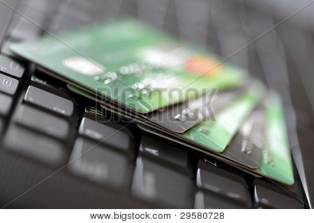 Credit cards on a laptop keyboard concept for e-commerce, consumerism or electronic banking