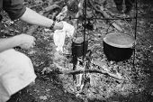 Re-enactor Dressed As World War Ii German Wehrmacht Soldier Cooking Food Over A Fire In An Old March poster