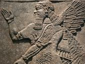 stock photo of mesopotamia  - Ancient Assyrian wall carvings of a man with long hair - JPG