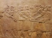 stock photo of sumerian  - Ancient Assyrian wall carvings of men on a Royal lion hunt
