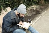 Poor Homeless Man With Book On Street In City poster