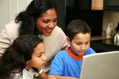 picture of mother child  - Mother and children in kitchen on the computer - JPG