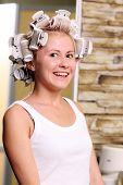 Young beautiful girl is having hair curlers on her head