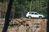 Woman Looking In Suv Car Trunk At Rocky Cliff. Travel Concept poster