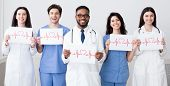 Doctors Holding Papers With Cadiograms Of Heartbeat, Grey Background poster