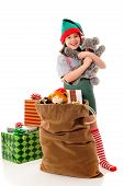 stock photo of christmas-present  - A Christmas elf hugging a plush animal before putting it into Santa - JPG
