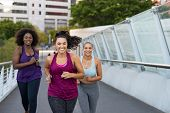 Happy young curvy women jogging together on city bridge. Healthy girls friends running on the city s poster