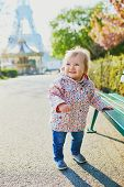One Year Old Girl Standing Next To A Bench In Paris, With The Eiffel Tower Behind Her. Little Kid En poster