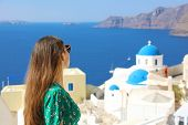 Santorini Travel Tourist Woman Visiting Oia, Famous White Village With Blue Domes In Greece. Girl In poster
