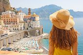 Summer Holiday In Italy. Back View Of Young Woman With Straw Hat And Yellow Dress With Atrani Villag poster