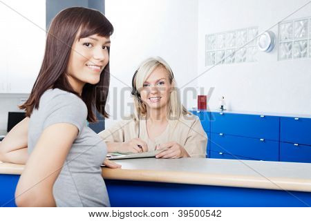 Portrait of young woman with receptionist filling form at desk in dentist's office