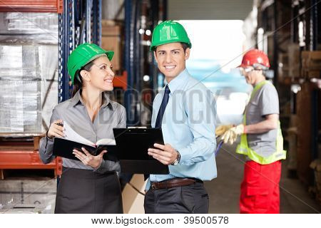 Portrait of male supervisor with colleague and foreman working at warehouse
