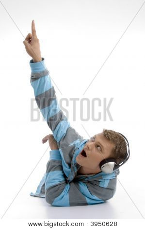 Laying Young Man With Headphone Indicating Upward