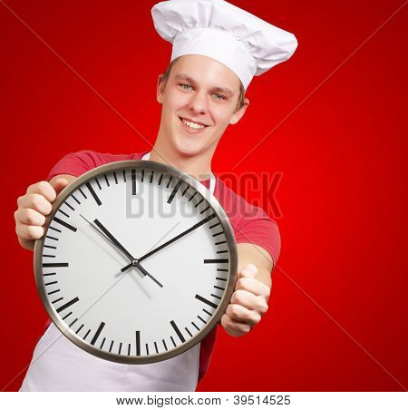 portrait of young cook man holding clock over red background