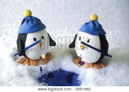Two Small Toy Penguins Fishing