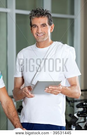 Portrait of happy mature man using digital tablet in health club