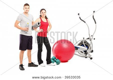 Full length portrait of a male and female athlete posing next to an excerise equipment isolated on white background