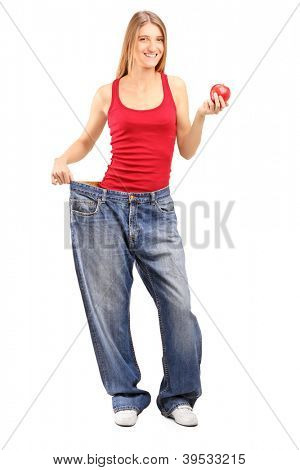 Full length portrait of a happy weight loss female holding her old jeans and apple isolated on white background