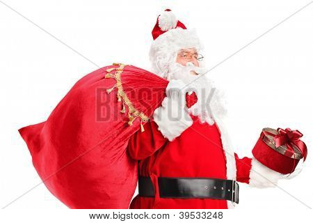 A Santa Claus carrying a bag full of gifts on his back isolated on white background