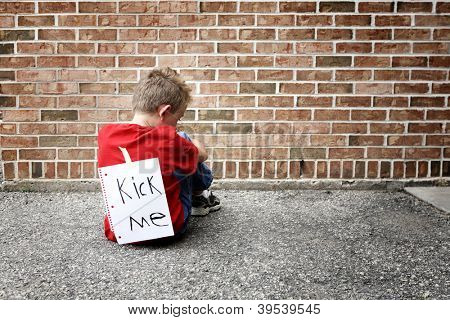 Sad boy sitting with a kick me sign on his back