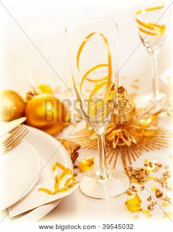 Picture of luxury festive table setting, closeup image of beautiful white utensil decorated with golden shiny toys and candle, romantic dinner in restaurant, New Year eve, Christmas holiday