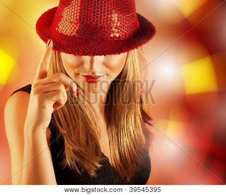 Image of luxury singer girl isolated on blur background, closeup portrait of pretty woman wearing red hat which covered her eyes, gorgeous dancer enjoying music in night club, New Year celebration