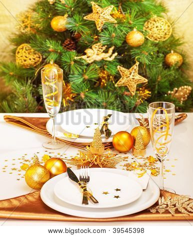 Picture of Christmastime table setting, luxury white plates served with knife and fork, two glasses for wine decorated with golden ribbon, Christmas tree adorned with stars, baubles and angel