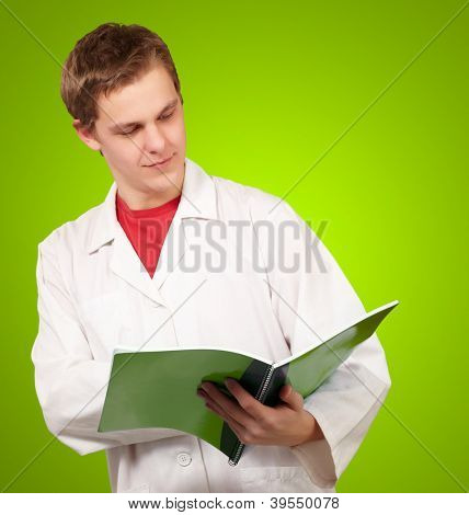 Portrait of a young doctor reading a folder on green background