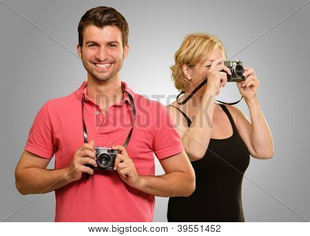 Young Man And Mature Woman Holding Camera On Gray Background