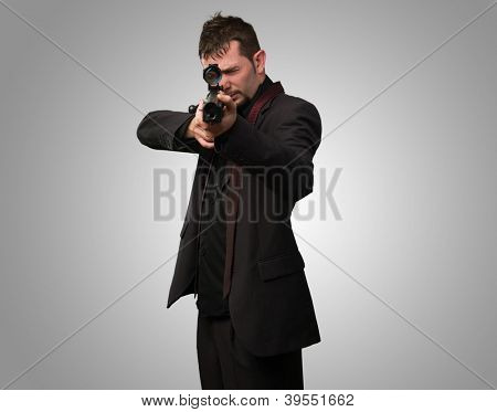 Man aiming with rifle against a grey background