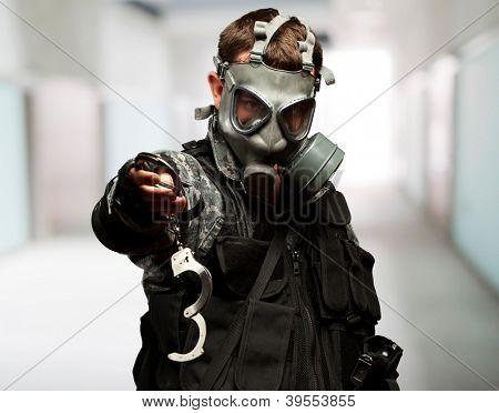 Soldat mit A Gasmaske Holding Handschellen vor einem abstrakten Hintergrund