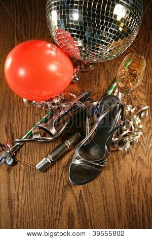 Party shoes on wood floor with champagne glass