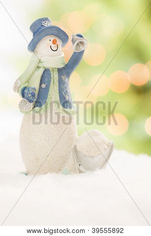 Snowman Statue On Snow Over a Blurry Abstract Green and Gold Background.