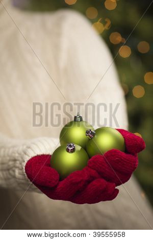 Woman Wearing A Sweater and Seasonal Red Mittens Holding Three Green Christmas Ornaments.