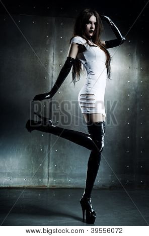 Young sexy goth woman on wall background.