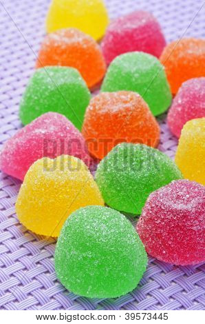gumdrops of different colors on a purple woven background