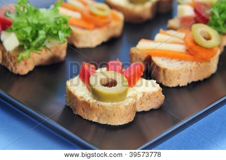 closeup of a black plate with different canapes