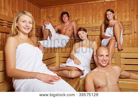 Smiling men and women sitting in a mixed sauna
