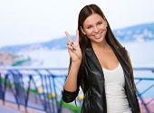 Young Woman Giving Victory Sign, outdoor